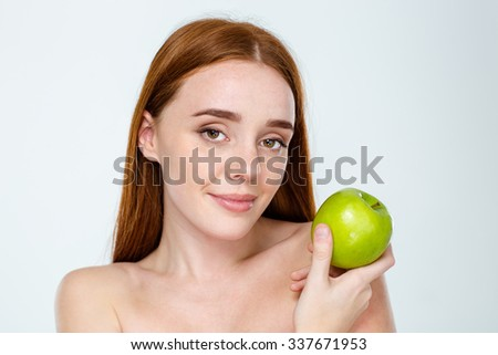 Beauty portrait of a attractive redhair woman with skincare holding apple isolated on a white background - stock photo