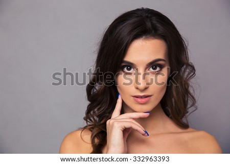 Beauty portrait of a charming woman looking at camera over gray background - stock photo