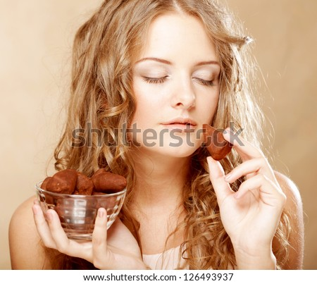 beauty portrait of a cute blond girl in act to eat a chocolate candy - stock photo