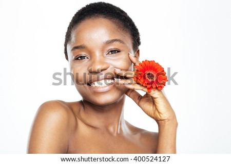 Beauty portrait of a happy afro american woman with flower looking at camera isolated on a white background - stock photo
