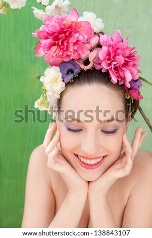 Beauty portrait of a retro young woman wearing a spring flowers hair dress against a green fabric background and smiling with her hands around her face. - stock photo
