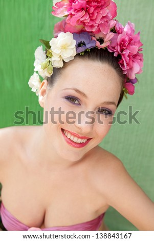 Beauty portrait of a retro young woman wearing a spring flowers hair dress while wearing a pink top, standing against a green fabric background, smiling. - stock photo