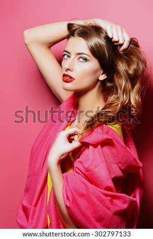 Beauty portrait of a sensual young woman in bright crimson headscarf over pink background. Beauty, fashion. Cosmetics. - stock photo