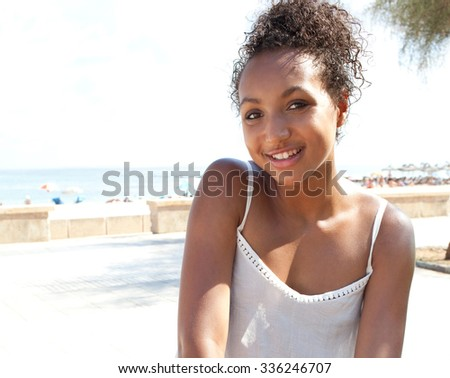 Beauty portrait of a young African American black adolescent girl by the sea coast on beach holiday during a sunny day, outdoors. Teenager travel and relaxing lifestyle, summer destination exterior. - stock photo