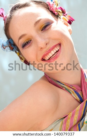 Beauty portrait of a young fresh woman wearing spring make up and head dress with flowers and butterflies, laughing leaning her head back against a blue background during a sunny day. - stock photo