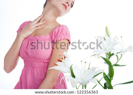 Beauty portrait of a young woman smelling a bunch of white lilies flowers, isolated on a white background. - stock photo
