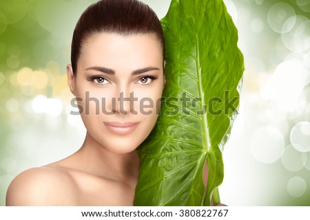 Beauty portrait of an attractive natural young girl with a large fresh green leaf held to her cheek against a soft green bokeh background in a spa and wellness concept - stock photo