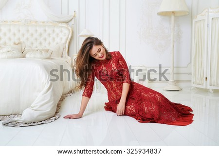 Beauty portrait of an attractive young woman laying in bedroom wearing a red dress and gently smiling - stock photo