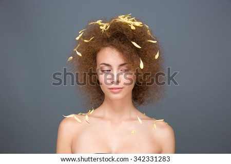 Beauty portrait of beautiful sensual gorgeous young woman with petals on voluminous curly hairstyle posing on gray background - stock photo