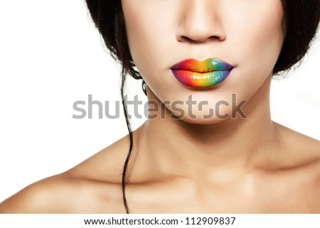 Beauty portrait of beautiful young mulatto fresh woman with rainbow lipstick, detail of face and shoulders closeup over white background - stock photo