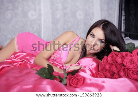 Beauty portrait of brunette girl with pink Roses lying on the bed. Valentines day - stock photo