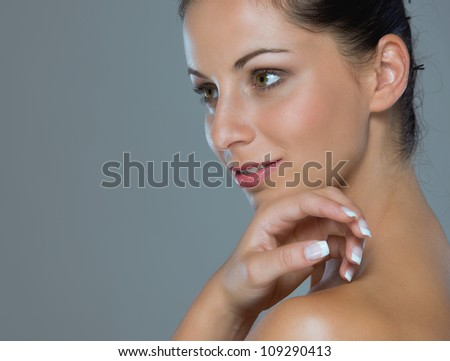 Beauty portrait of girl showing well-groomed hands on gray - stock photo