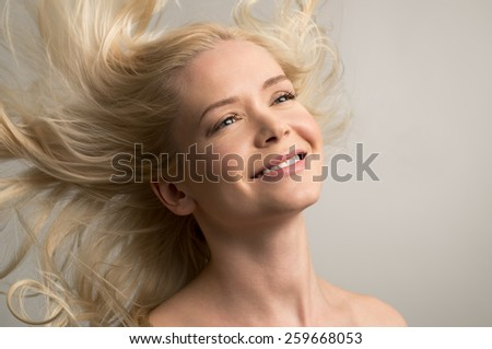 Beauty portrait of smiling young woman with wind in the hair  - stock photo