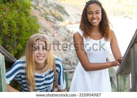 Beauty portrait of two young teenager girls of different ethnic origins friends smiling together by the sea on a summer holiday, outdoors. Travel fun and adolescent lifestyle, nature beach exterior. - stock photo