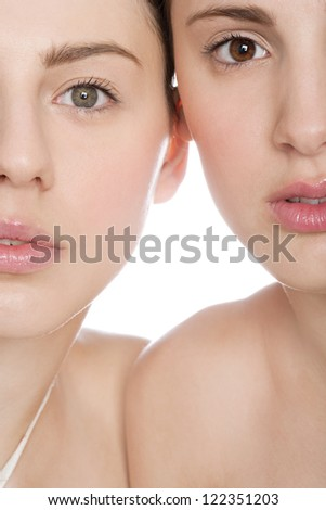 Beauty portrait of two young women half faces next to each other and wearing glossy lipstick, against a back lit white background. - stock photo