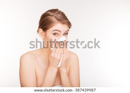 Beauty portrait of unhappy young woman catched a cold and using paper handkerchief over white background - stock photo