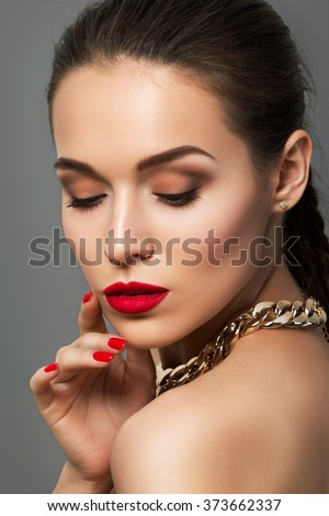 Beauty portrait of young aristocratic woman with red lips and nails. Classic evening make up. Brown smokey eyes - stock photo
