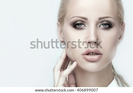 Beauty portrait of young attractive blonde woman with natural makeup. Beautiful female face. Closeup photo. Fashion model with blue eyes looking at camera. - stock photo