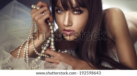 Beauty portrait of young beautiful brunette woman with pearls. Girl looking at camera. - stock photo