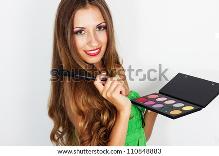 beauty portrait of young beautiful woman with makeup brush and palette of eye shadows isolated on white background - stock photo