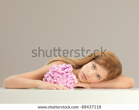 beauty portrait of young, blonde woman resting her head on her arm, holding a pink hydrangea - stock photo