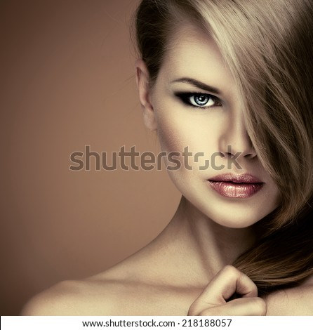 Beauty portrait of young lovely woman with perfect long straight hair looking at camera. Pretty Caucasian girl with professional smoky eyes make up posing in studio.   - stock photo