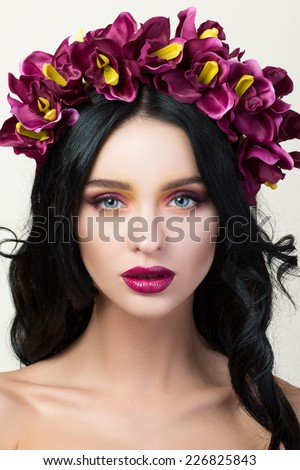 Beauty portrait of young pretty brunette girl with flower wreath in her hair - stock photo