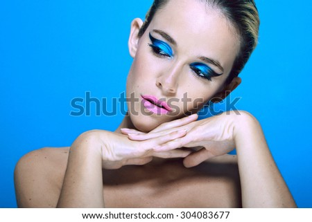 Beauty portrait  of young sexy woman against light blue background - stock photo
