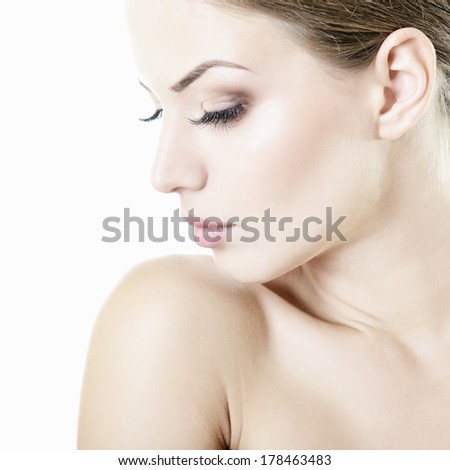 Beauty portrait of young woman with beautiful healthy face in profile, studio shot of attractive girl over on white background. High key - stock photo