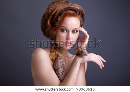 Beauty portrait on young stylish woman with creative hairstyle  and with snails - stock photo