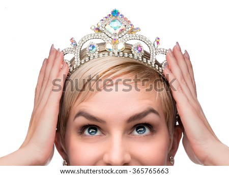 Beauty queen pageant winner placing tiara on head celebrating individuality independence courage and high self esteem - stock photo
