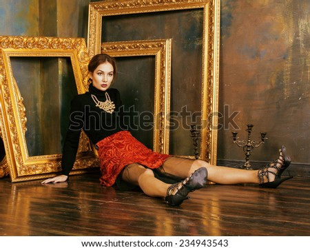 beauty rich brunette woman in luxury interior near empty frames, vintage elegance, gold - stock photo