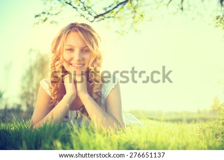 Beauty Romantic Girl lying on summer field Outdoors. Nature. Beautiful young Model Woman with long curly hair Smiling. Cute Teenage Girl lying on grass. Meadow. Grassland. Allergy free. Sunshine - stock photo