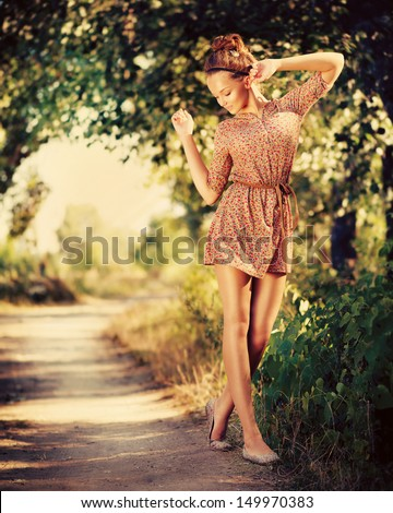 Beauty Romantic Girl Outdoor. Beautiful Teenage Model Dressed in Fashionable Short Dress Posing Outdoors in Sun Light. Full Length Portrait. Toned in warm colors. Fashion Look - stock photo