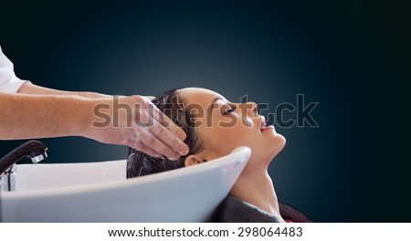 beauty salon and people concept - happy young woman and hairdresser hands washing head and hair over blank black background - stock photo