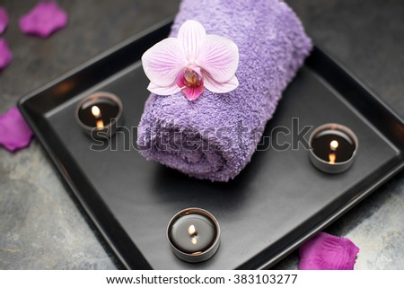 Beauty salon decoration in massage room, candles, towel and orchid. - stock photo