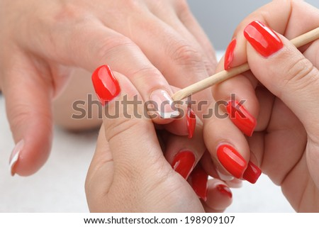 beauty salon, manicure applying, cleaning the cuticles - stock photo