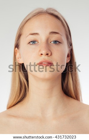 Beauty shoot of a young pretty girl nude. Blue eyes, blond hair, wearing no make-up in her perfect clear skin. Cosmetic advertisement style. Natural scandinavian face of a woman looking a t camera - stock photo
