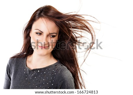 Beauty shot of a beautiful, long haired, brunette woman with her hair fluttering. - stock photo