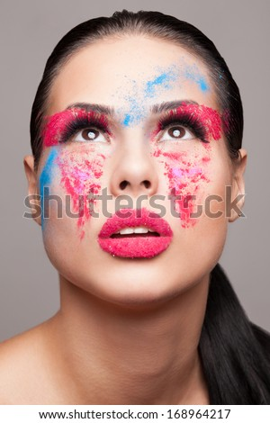 Beauty shot of fashionable women face with pink, red and blue dry powder. red glitters on lips. FaceArt - stock photo
