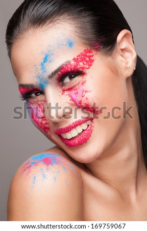 Beauty shot of smiling face with pink, red and blue dry powders. red glitters on lips. FaceArt - stock photo