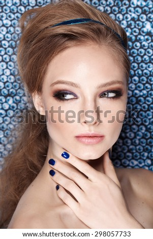 beauty shot of young pretty model with blond hair and blue nails. Manicure - stock photo