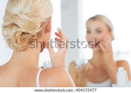 beauty, skin care and people concept - close up of smiling young woman applying cream to face and looking to mirror at home bathroom - stock photo