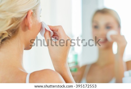 beauty, skin care and people concept - close up of smiling young woman cleaning her face with cotton disc and lotion at bathroom - stock photo