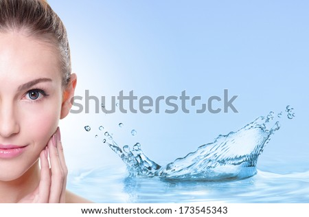Beauty Skin care concept, Beautiful woman face with Water splashes isolated on blue background - stock photo