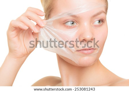 Beauty skin care cosmetics and health concept. Closeup young woman face, girl removing facial peel off mask isolated on white. Peeling - stock photo