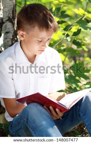 Beauty smiling child boy reading book outdoor on green park - stock photo