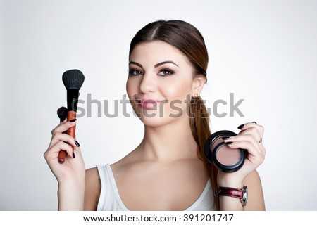 Beauty smiling happy Girl make up artist with Makeup Brush. Bright Holiday Make-up for Brunette Woman with Brown Eyes.  Beautiful Face. Makeover. Perfect Skin. Applying Makeup - stock photo