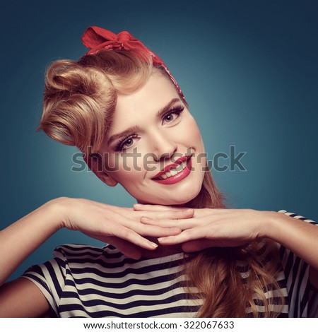 Beauty smiling pin-up girl on blue background. Sexy woman in pinup style, toned. - stock photo