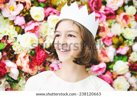 Beauty smilling teen age girl in white crown over flower wall - stock photo